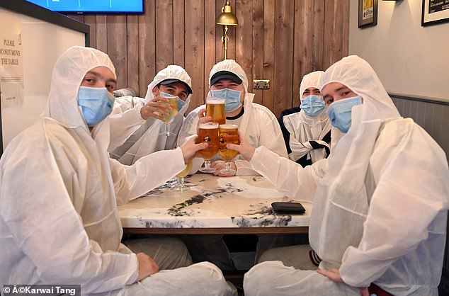 Five pub-goers dressed in protective suits and with face masks enjoy their first pub pint since March at The Wellington pub in Borehamwood welcomes its first customers since lockdown began