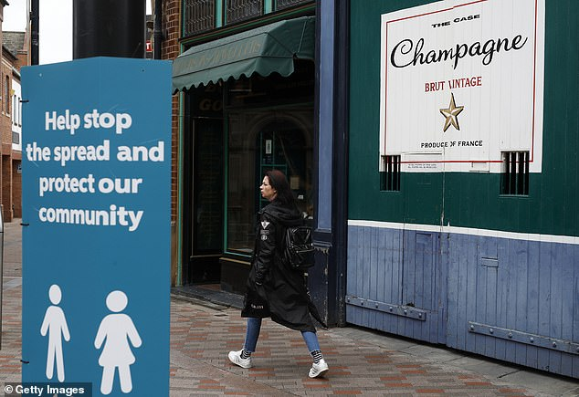 A woman walks past a closed champagne bar during local lockdown in Leicester on Saturday