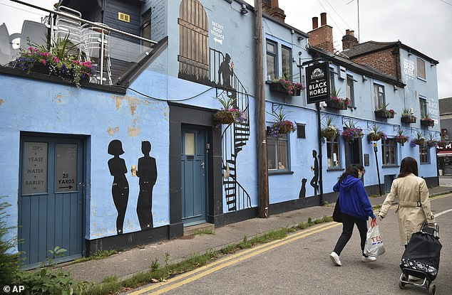 People walk past the still-shut Black Horse pub inside the lock down zone in Leicester