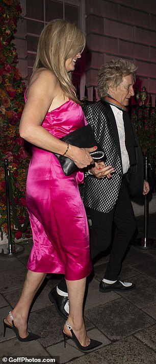 Chic: But his model wife, 49, stole the show in a striking fuchsia satin midi dress, which boasted tie-wrap detailing around the waist