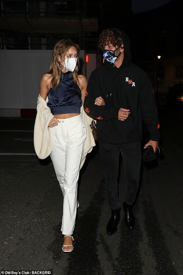 Stepping out: The couple looked stylish as they left the Treehouse Hotel in Marylebone with Eyal wearing a lightning bolt mask and Delilah opting for a simple white design