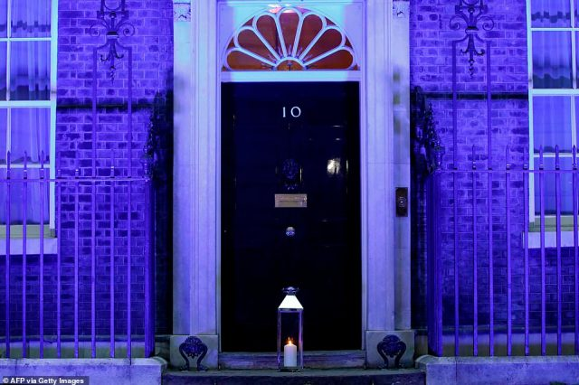 A candle is lit and placed on the doorstep of 10 Downing Street in central London on July 4, 2020 in honour of the tens of thousands of people who have died as a result of the coronavirus pandemic in the UK as the building itself is lit up blue as a tribute to NHS workers and to mark the 72nd anniversary of the NHS