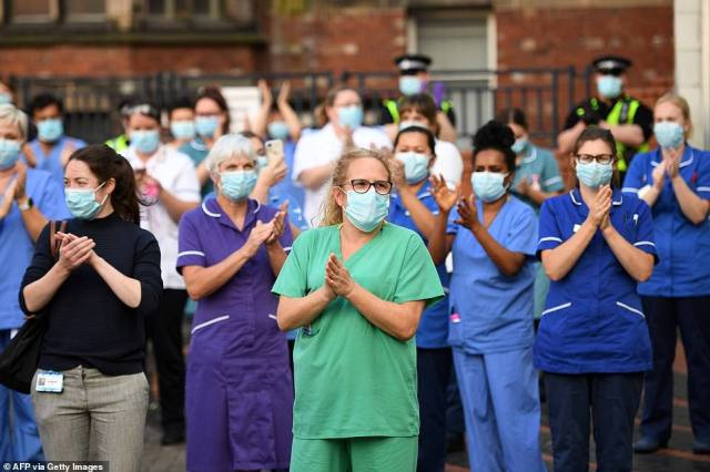Members of the emergency services and staff of the Leeds General Infirmary participate in a national NHS celebration clap outside the hospital in Leeds today, to mark its 72nd anniversary