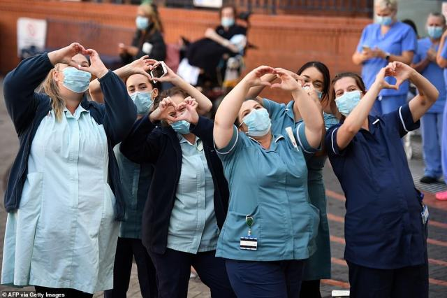Members of staff of the Leeds General Infirmary gesture to their colleagues from the street as they all participate in a national NHS celebration clap