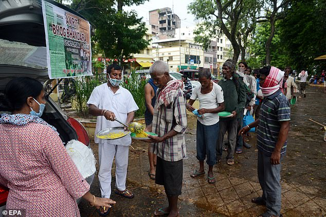 India has overtaken Russia to become the country with the third highest number of coronavirus cases in the world, with nearly 700,000 infections.  Above, volunteers distribute free food during the pandemic in Guwahati on July 5