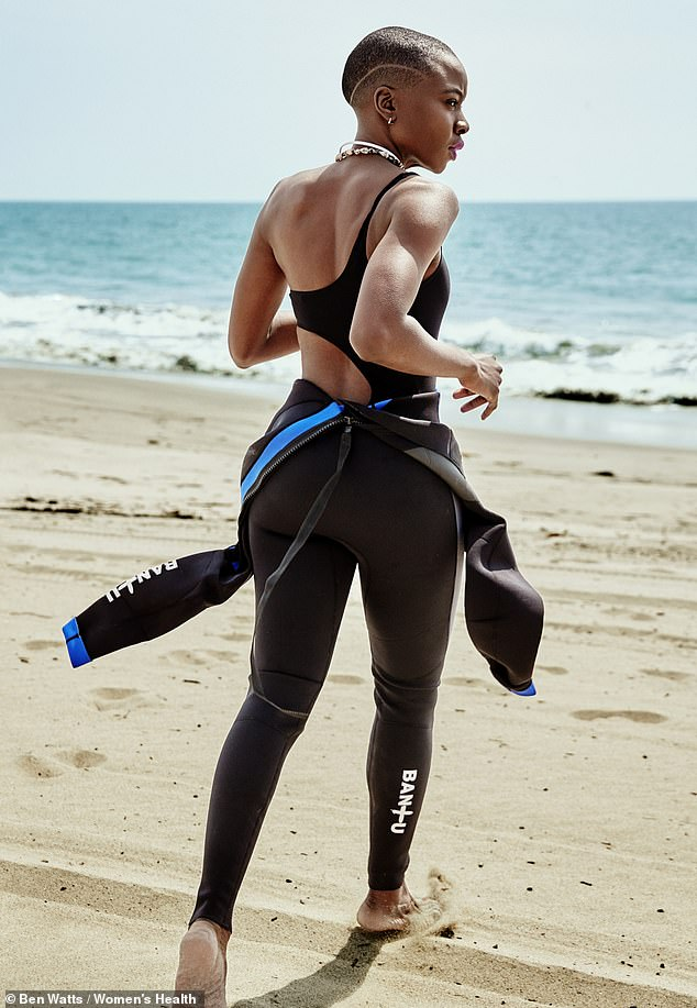 Powerful: In one shot, Danai showed off her athletic form while running along the beach in a swimsuit and wetsuit
