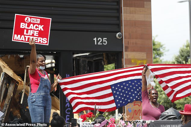 Protesters chant outside a Wendy's restaurant on June 23 after a funeral for Rayshard Brooks was held