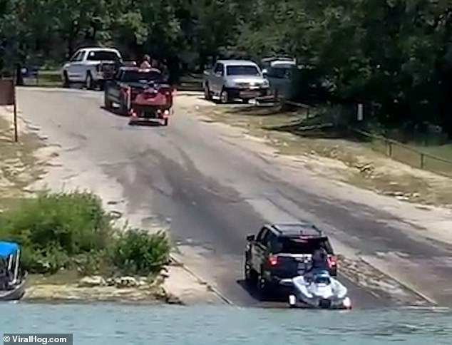 A black pickup truck towing a jet ski trailer pulls up at the top of a ramp at Canyon Lake, Texas, to try and reverse it down to the water