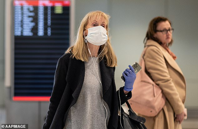A passenger wearing a protective masks arrives on a flight from Melbourne into Sydney on Tuesday. The federal government is due to review JobKeeper later this month