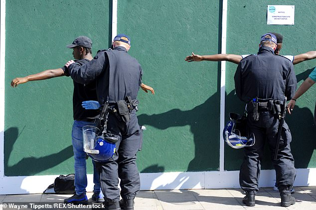 A report from the Commons home affairs committee found last week that the use of stop and search was more racially disproportionate now than 20 years ago (Pictured: Two men being searched by officers during the Notting Hill Carnival in August 2017)
