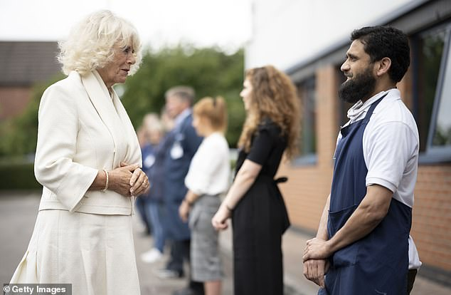 Camilla speaks to a worker during a visit with Prince Charles to the Turnbull & Asser shirt factory in Gloucester today