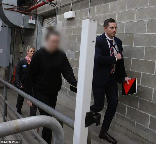 Young is seen as she was marched into the police station to be charged