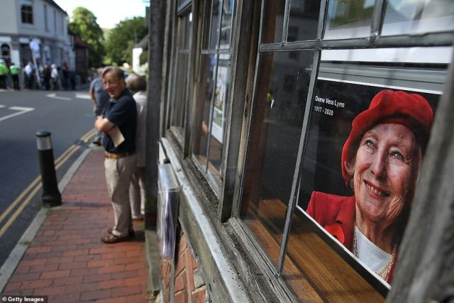 Dame Vera Lynn's photograph is displayed in a window as people line the high street in Ditchling, West Sussex, ahead of her funeral