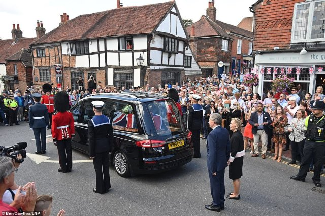 A hearse carrying the coffin passes through the town of Ditchling, East Sussex as members of the public gather to pay their respects ahead of the funeral of Dame Vera Lynn today