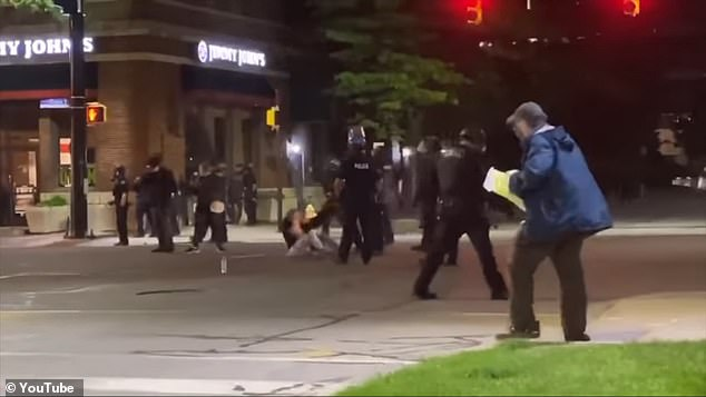 An unidentifiedErie Bureau of Police officer was caught on camera kicking a women in the shoulder after she was maced in Erie, Pennsylvania (pictured)