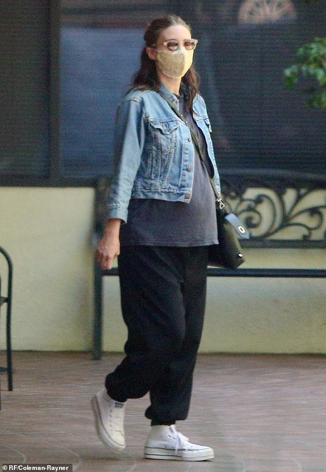Baby bump:The 35-year-old Girl With The Dragon Tattoo star attempted to keep her growing baby bump concealed beneath an oversized grey tee and a cropped denim jacket