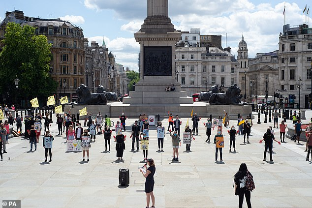 Protesters holding signs gather around Nelson's Column in Trafalgar Square today to protest against animal farming