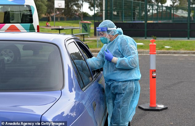 A medical worker is pictured performing a COVID-19 test as Melbourne re-enters stage three lockdown restrictions