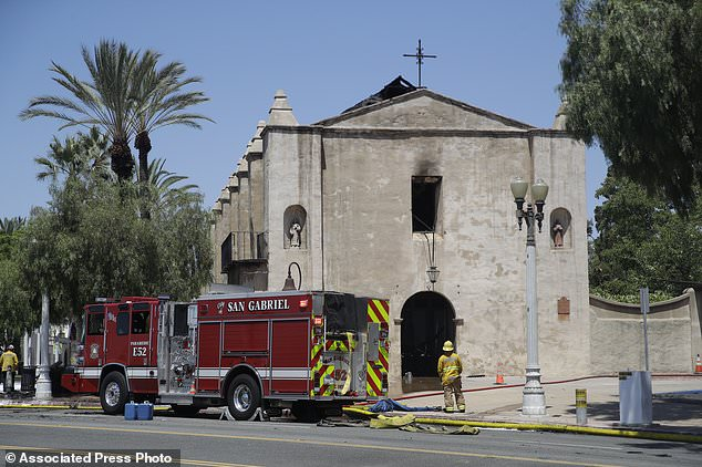 A firefighter stands outside the San Gabriel Mission in the aftermath of a fire, Saturday, July 11, 2020, in San Gabriel, Calif. The fire destroyed the rooftop and most of the interior of the nearly 250-year-old California church that was undergoing renovation