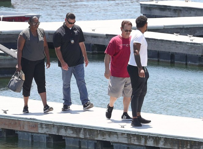 Naya Rivera's mother, Yolanda and her son, Mychal, far right, along with a police officer were pictured walking along the jetty