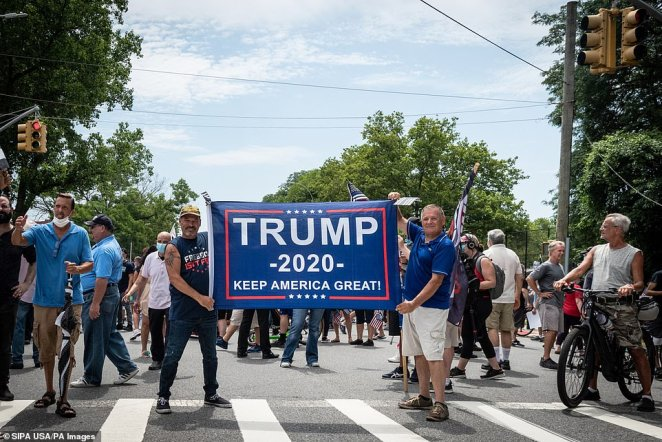 Two men hold up a 'Trump 2020 - Keep America Great' bannerduring a Blue Lives Matter rally in Bay Ridge, Brooklyn, on Saturday