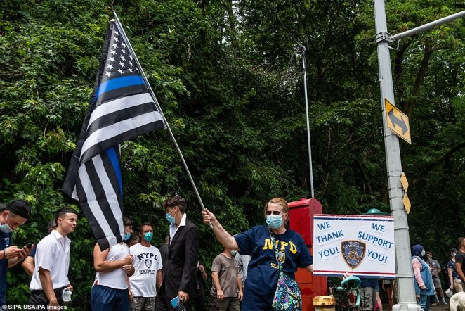 A woman holds a thin blue line flag and a sign that reads 'We thank you! We support you!' with an NYPD logoduring a Blue Lives Matter rally in Bay Ridge, Brooklyn, on Saturday
