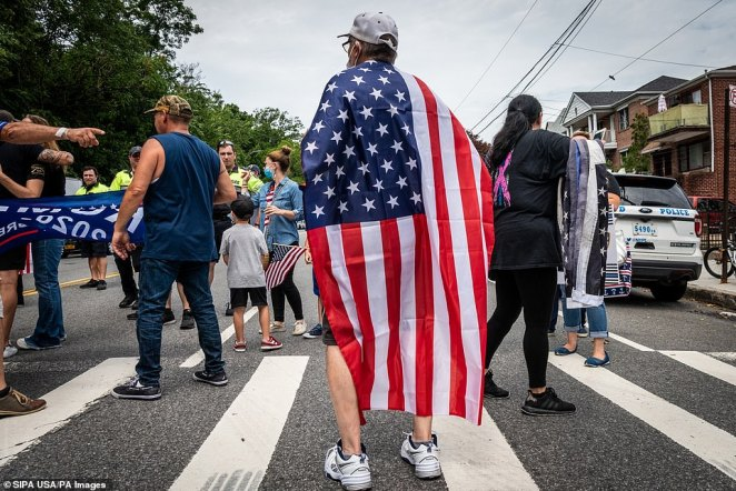 One man dons an American flag as he looks onduring a Blue Lives Matter rally in Bay Ridge, Brooklyn, on Saturday