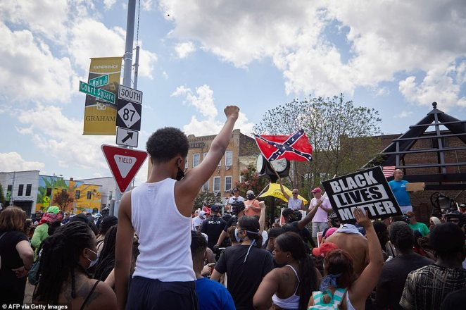 Anti-racist protesters raise fists toward supporters of the Confederacy at the Alamance County Courthouse at at a rally with the Burlington-Alamance March For Justice and Community in Graham, North Carolina, on Saturday