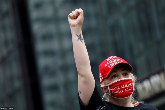 A supporter of the president wearing a red 'Keep America Great' hat and a 'Make America Great Again' face covering gesturesduring a demonstration in front of Trump Tower in New York City on Saturday