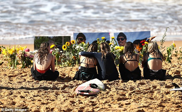 Friends pay their respects in memory of Alex 'Chumpy' Pullin at North Narrabeen Beach on July 12