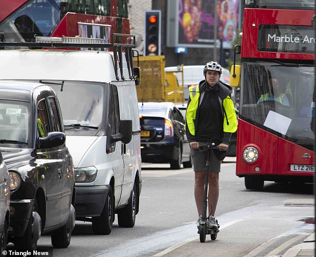 Man wearing shorts, hi-vis jacket and helmet rides his e-scooter in front of a bus