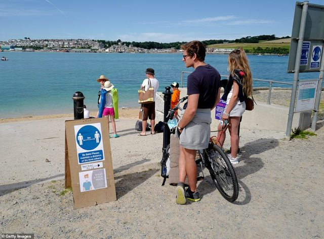 A man on a bike reads a social distancing sign as he waits for the ferry from Rock to Padstow today ahead of a warm afternoon