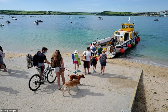 Holiday-makers line up and wait for the Rock to Padstow ferry across the bay today in Cornwall