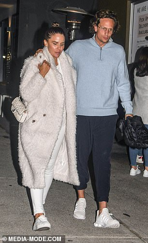Attire: He wore a pale blue sweater, cropped black pants and pristine white sneakers