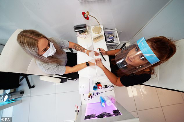 Beautician Alex Smith, 26, does the nails of Jules Aspen, 40, at the Madame Beauty salon in Chirton, North Tyneside
