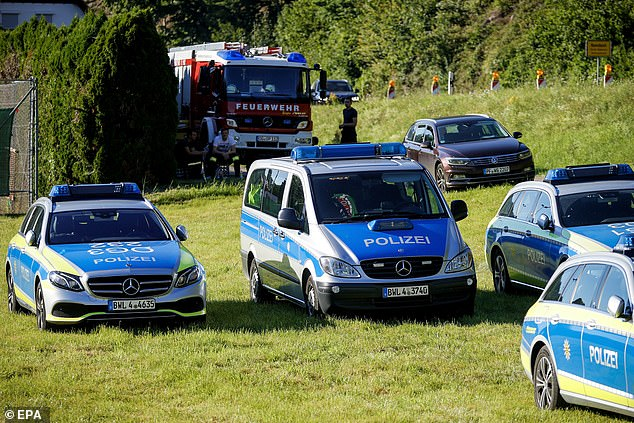 Authorities took the unusual step of naming the suspect as Yves Etienne Rausch, 31, warning that he is carrying several firearms and known to be violent. Pictured: Police vehicles involved in the search