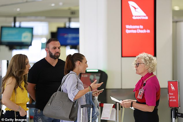 Ninety per cent of Qantas frequent flyers have shown an interest to travel despite COVID-19. Pictured: Travellers chat with Qantas staff at Sydney airport on March 19