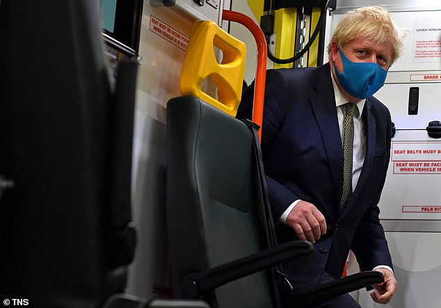 Prime Minister Boris Johnson, wearing a face mask, boards an ambulance to talk with a paramedic during a visit to the headquarters of the London Ambulance Service NHS Trust on Monday