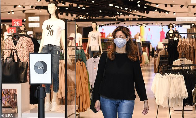 A customer wearing a face mask at a store in London on Tuesday. They will soon be mandatory from July 24 onwards