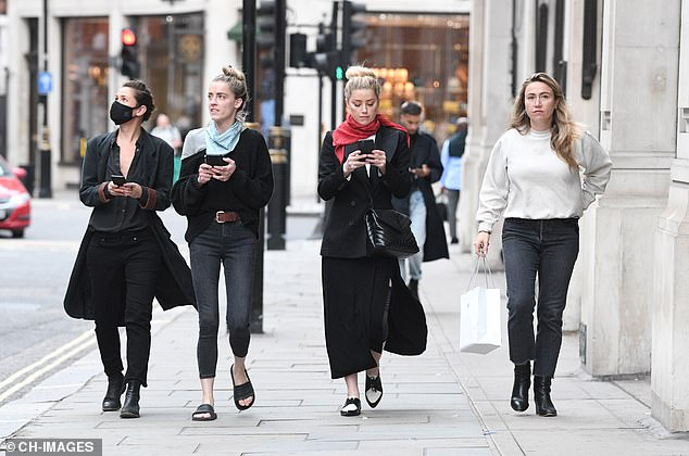 The group removed their masks as they walked around the Capital, with Heard's assistant clutching a shopping bag