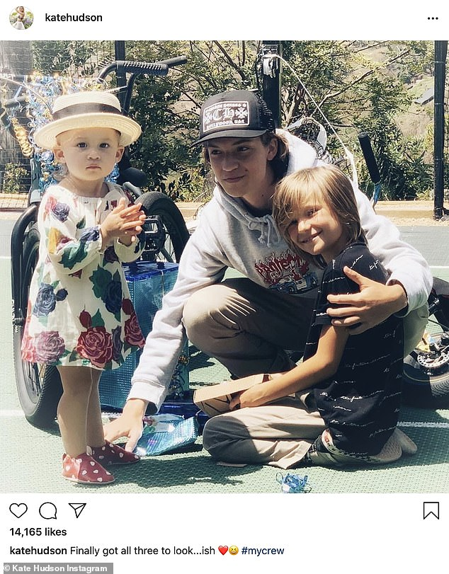 'My crew':Kate Hudson shares an adorable photo of her kids bonding together on Wednesday, captioning the post: 'Finally got all three to look...ish'