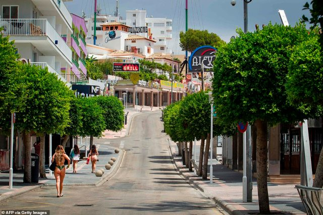 A few solo tourists stroll along the Punta Ballena street in Magaluf
