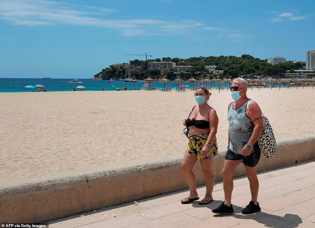 Tourists walk at Magaluf beach - which would usually be jam packed at this time of the year