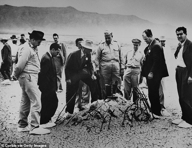 Robert Oppenheimer and General Leslie Groves (center) examine the twisted wreckage that is all that remains of a hundred-foot tower, winch, and shack that held the first nuclear weapon