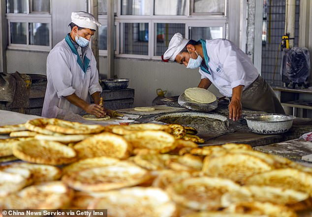 China has implemented what provincial officials have called the toughest anti-virus measures on the capital of Xinjiang as the region prepares for an impending COVID-19 epidemic.  Photo taken on June 17 shows workers making a type of traditional oven pancake at a poverty alleviation workshop in Keping County, Xinjiang Uighur Autonomous Region of China