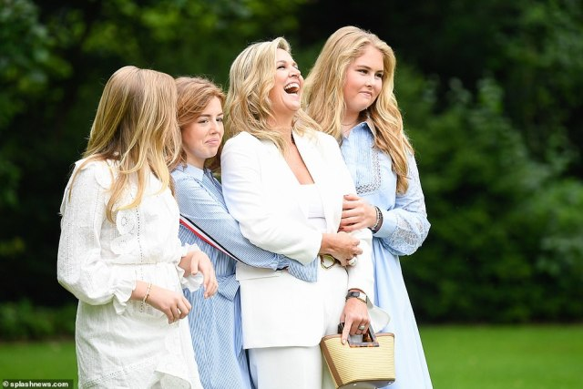 Perfect princesses! Maxima held onto her purse and kept composed while giggling with her daughters, who matched in light blue and white in the gardens
