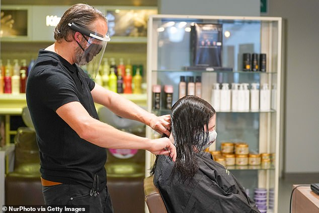 One in 10 Britons flocked to hairdressers and barbers to get their split ends and beards trimmed in the week after the coronavirus lockdown in England was eased (pictured,Conrad Blandford, owner of Conrad Blandford Hairdressing salon, Sheffield wears PPE and a protective face mask works with a client's hair in Sheffield)