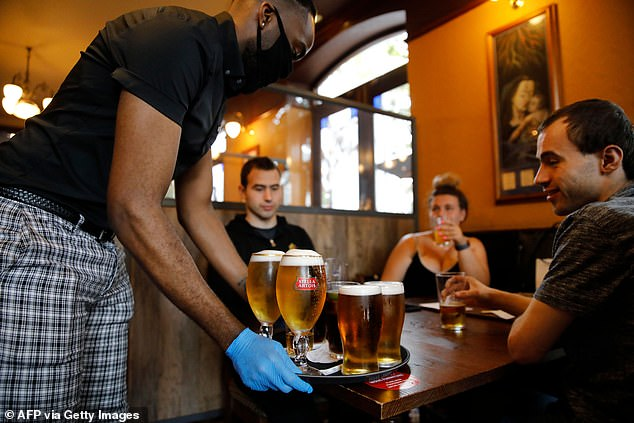 10 per cent ate or drank in a restaurant, cafe, bar or pub while 15 per cent collected takeaways, according to the Office for National Statistics. Nearly one third of people surveyed between July 8 and July 12 said they would eat at a restaurant in the next seven days, while the number of adults who feel uncomfortable about eating out fell by nearly 10 per cent (pictured, drinkers enjoying a round of beers inside a Wetherspoons pub in Stratford, London)