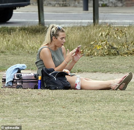 A woman is seen using her mobile phones as she enjoys glorious summer sunshine on Clapham Common today
