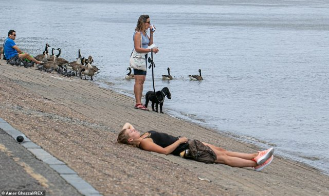 People gather along the Putney embankment as the Met Office charts showed temperatures of 72F in the south by Tuesday